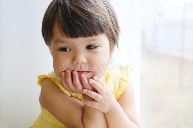 Att drömma liten flickaståenden lutar på armbågar på fönstret som längtar efter något le barnet som tänker om behaglig tanke royaltyfri bild