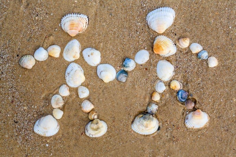 Att dra på sanden är det förälskade paret royaltyfria bilder