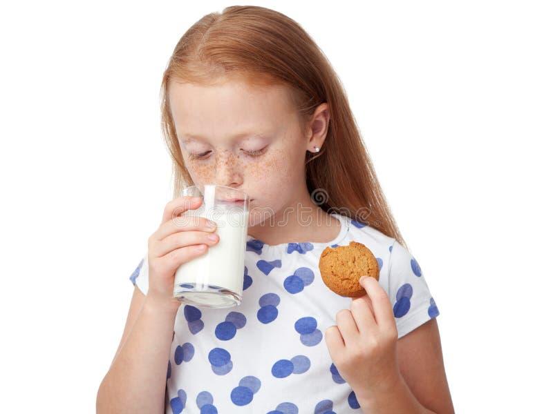 Att dricka för flicka mjölkar och att äta en kaka royaltyfria foton