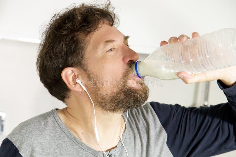 Att dricka för man mjölkar i morgonen i kök från flaskcloseupen arkivbild