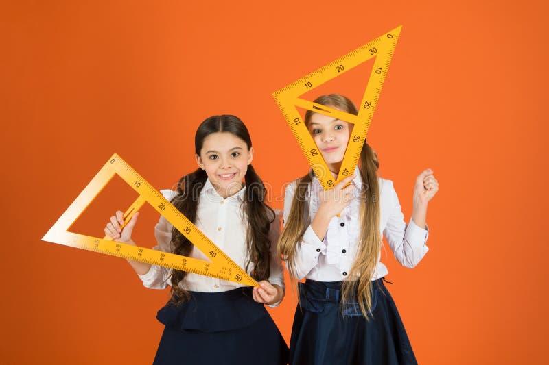 Att få tillbaka till fyrkanten rotar Små flickor ordnar till för geometrikurs Små flickor är tillbaka till skola skola arkivfoto