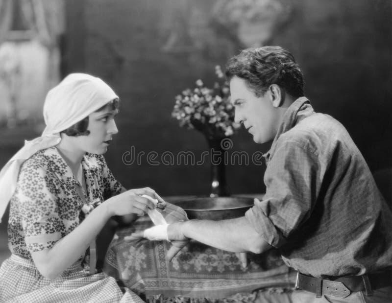 Att förbinda för kvinna mans handen (alla visade personer inte är längre uppehälle, och inget gods finns Leverantörgarantier att  royaltyfria foton