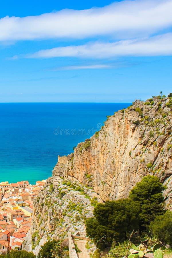 Att f?rbluffa sikt av det bl?a Tyrrhenian havet som tas fr?n ?ver med, vaggar och den kust- staden Cefalu i italienare Sicilien F arkivfoto