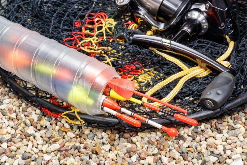 Att fiska svävar i lagringsasken med metspörullen och fiskbehållare på den steniga jordningen arkivfoton