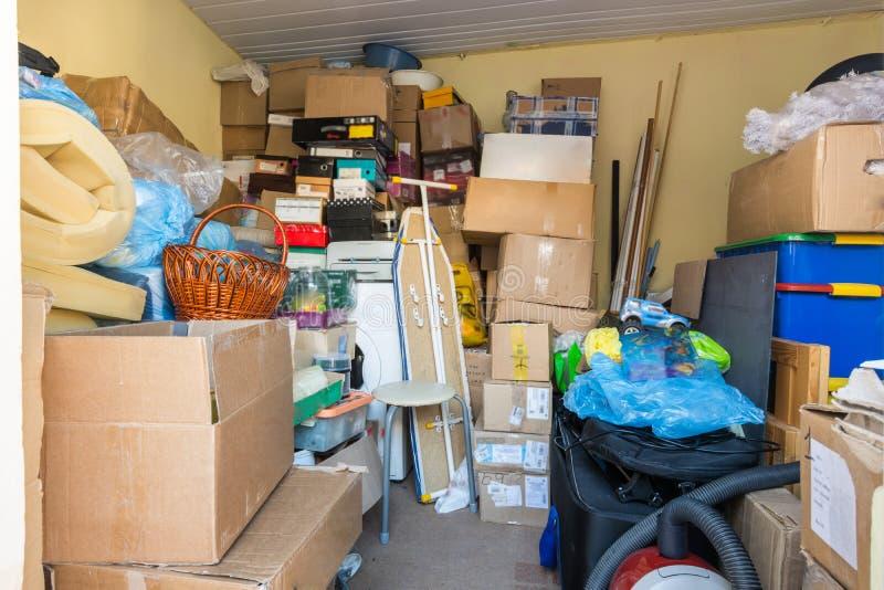 Att flytta sig, saker som packas i askar, och packar ligger i ett litet rum royaltyfri foto