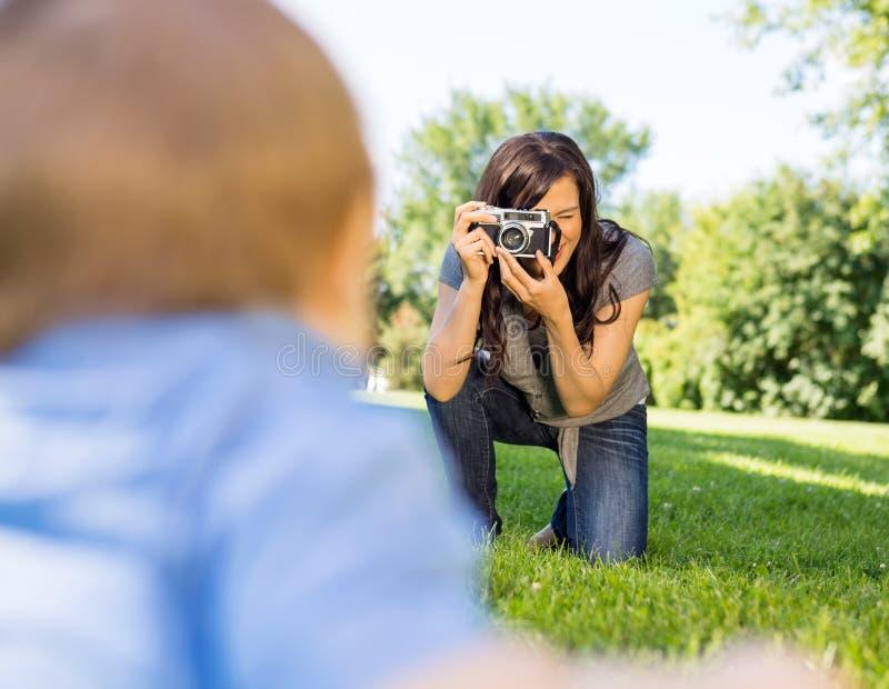 Att fotografera för kvinna behandla som ett barn sonen royaltyfria foton