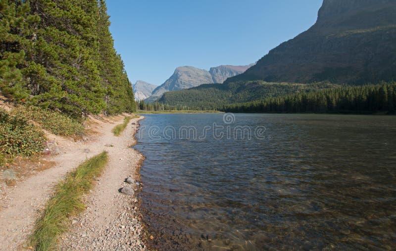 Att fotvandra släpar kusten av Fishercap sjön på Swiftcurrenten som fotvandrar slingan i glaciärnationalpark i Montana USA royaltyfri fotografi