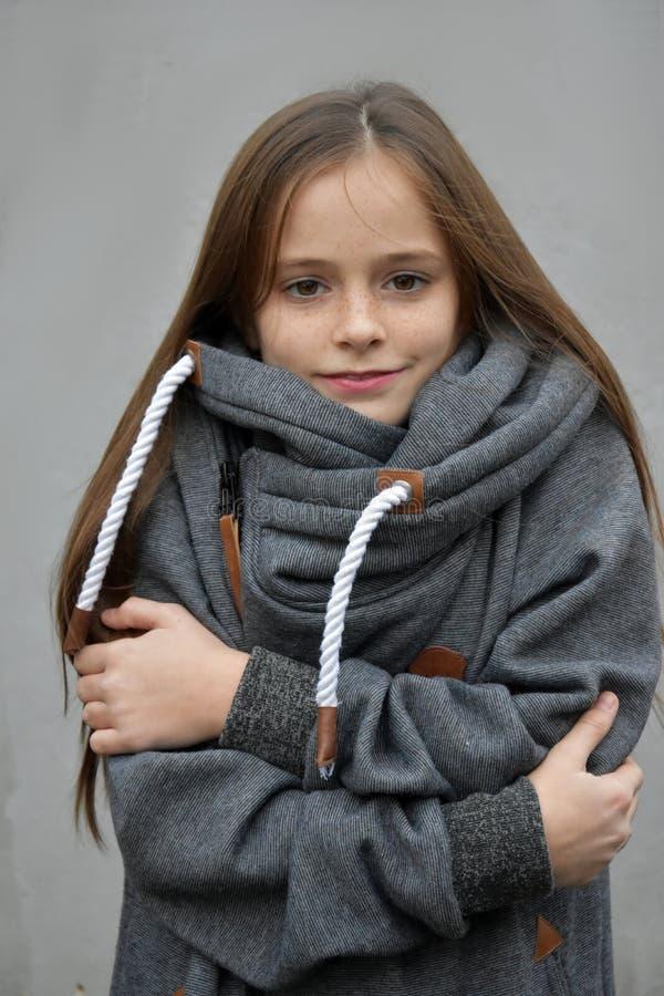 Att frysa flickan smyga sig i hennes woolen tröja arkivfoto