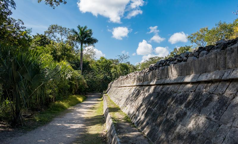 Att gå banan längs den forntida stenväggen bland Mayan fördärvar av Chich royaltyfri foto
