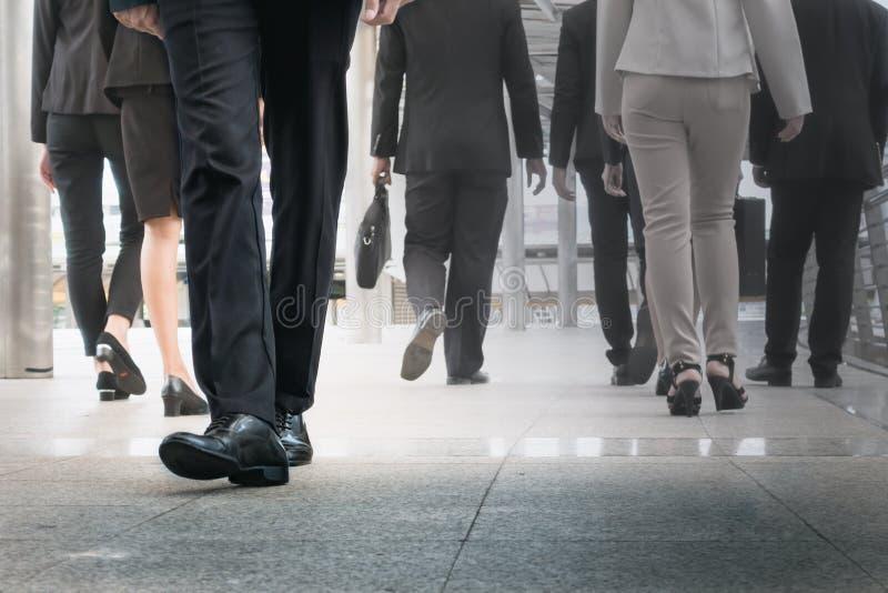 Att gå för affärsmanben går framåtriktat som utstående vid andra ben arkivbilder