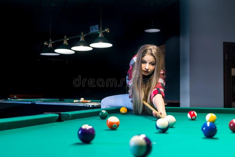 Att gå för kvinna slogg en boll med stickreplik i billiard fotografering för bildbyråer