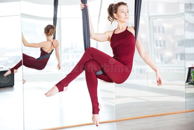 Att göra för den Attarctive kvinnan poserar av flyg- yoga genom att använda hängmattan royaltyfria foton