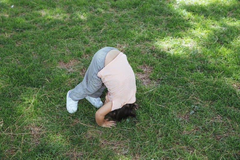 Att göra för flicka slår en kullerbytta på gräsmatta arkivbild