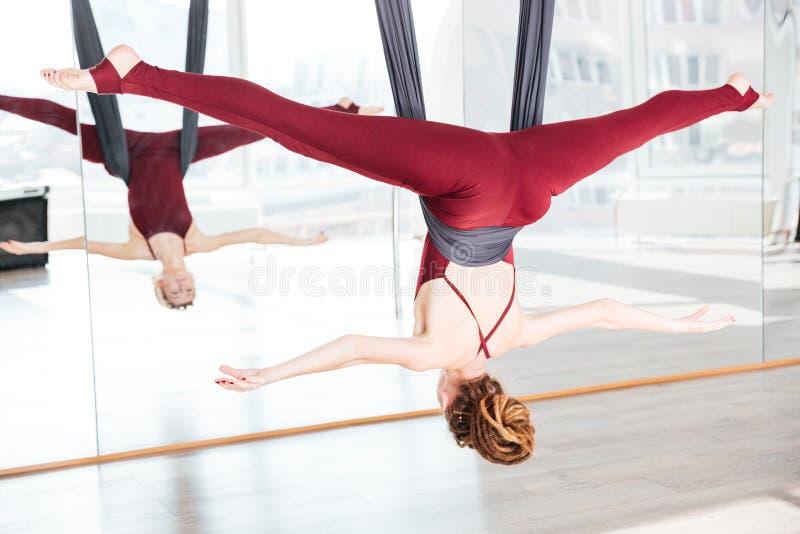 Att göra för kvinna poserar av antigravity yoga genom att använda hängmattan royaltyfri bild