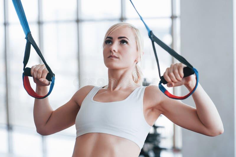 Att göra för kvinnor skjuter ups utbildningsarmar med trxkonditionremmar i sporten för livsstilen för idrottshallbegreppsgenomkör arkivfoton