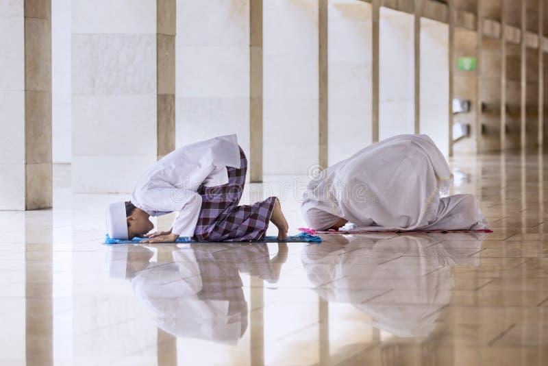 Att göra för ung man ber med hans fru i moskén arkivfoton
