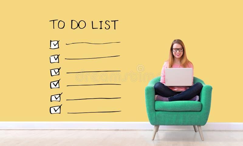 Att att göra listan med kvinnan som använder en bärbar dator arkivbild