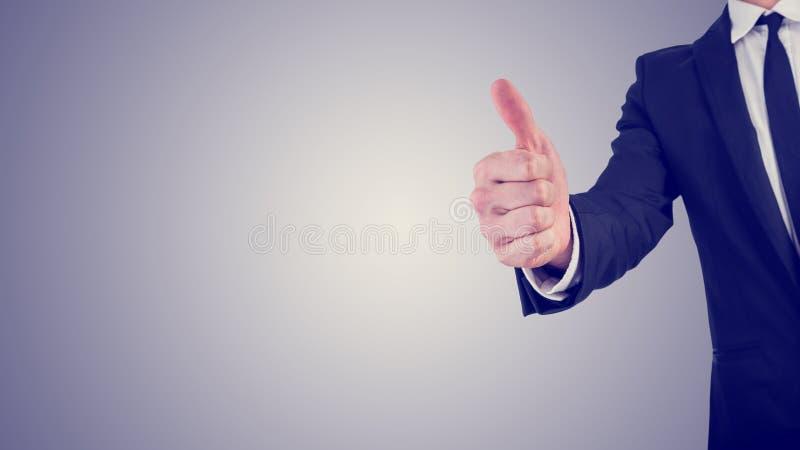 Att ge sig för affärsman tummar gör en gest upp i en affärsmotivation royaltyfri bild