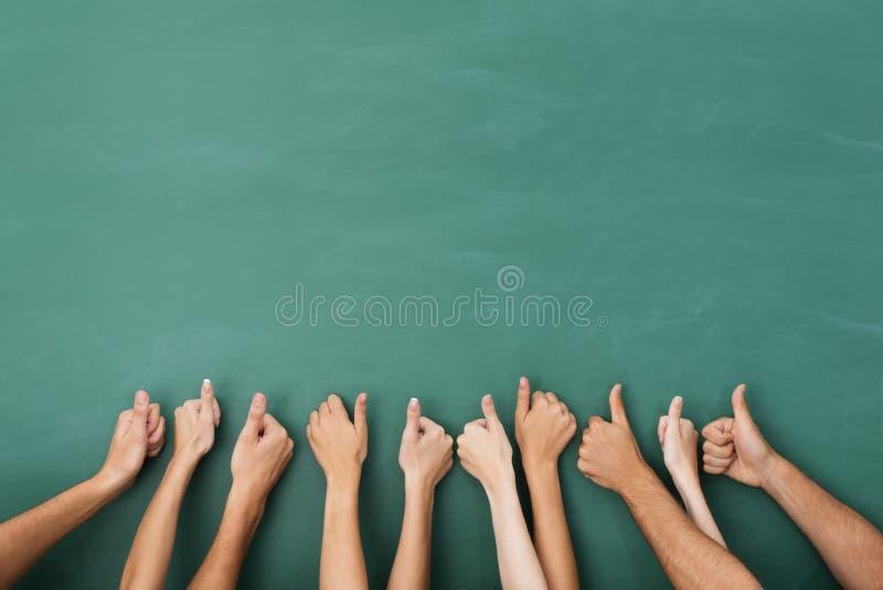 Att ge sig för grupp människor tummar gör en gest upp arkivbild