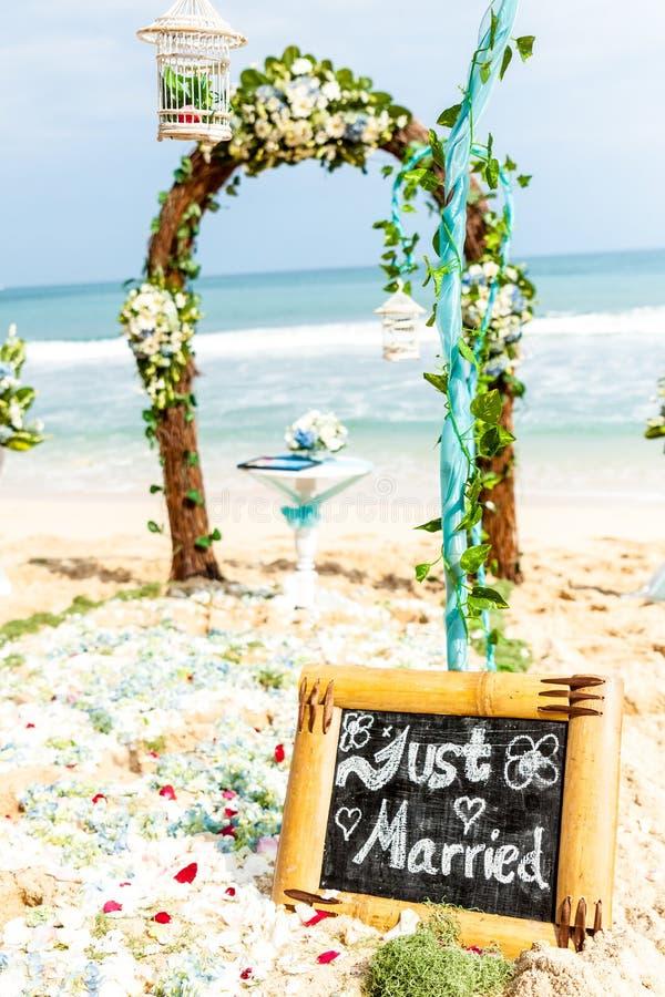 Att gifta sig bågen av blommor och murgrönan står på kuststranden arkivbild