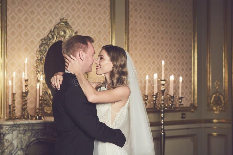 Att gifta sig par i en lyxig inre i den barocka stilen är att krama sig Härlig modellflicka i den vita klänningen arkivfoto