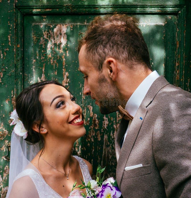 Att gifta sig par inomhus är att krama sig Härlig modellflicka i den vita klänningen Manen passar in Skönhetbrud med brudgummen arkivbilder