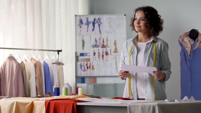 Att granska för modeformgivare skissar att tänka om hennes nya skapelse, inspiration royaltyfria bilder