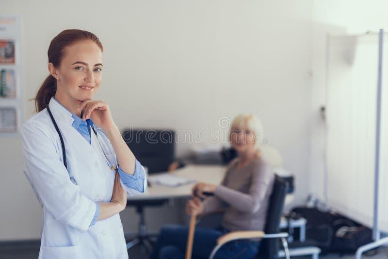 Att grina den kvinnliga läkaren behandlar patienten i sjukhuset arkivfoto