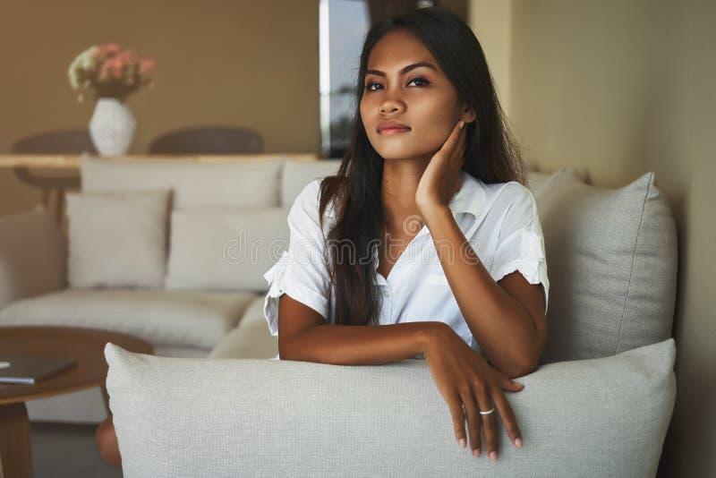 Att grubbla den unga asiatiska kvinnan är att placera på soffan hemma i vardagsrummet royaltyfria bilder