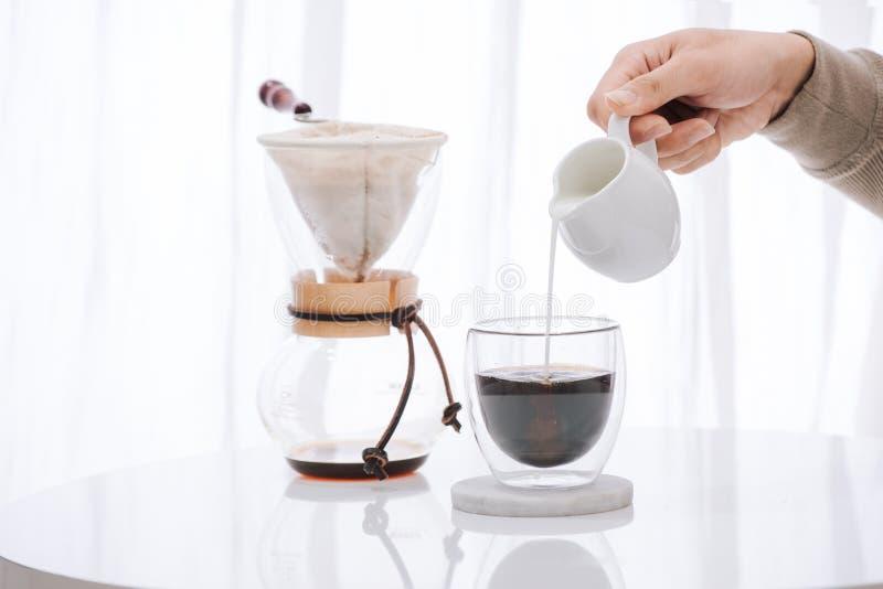 Att hälla för man mjölkar in i exponeringsglas med kallt brygdkaffe på tabellen royaltyfri fotografi