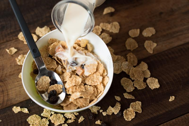 Att hälla mjölkar in i cornflakes för frukostsädesslag royaltyfria foton