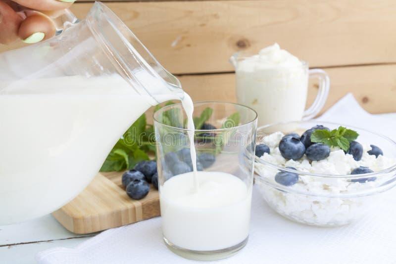 Att hälla mjölkar i exponeringsglaset på tabellen arkivbild