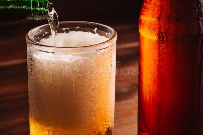 Att hälla skumma öl in i exponeringsglas rånar med droppar nära bootle för kallt öl arkivfoto