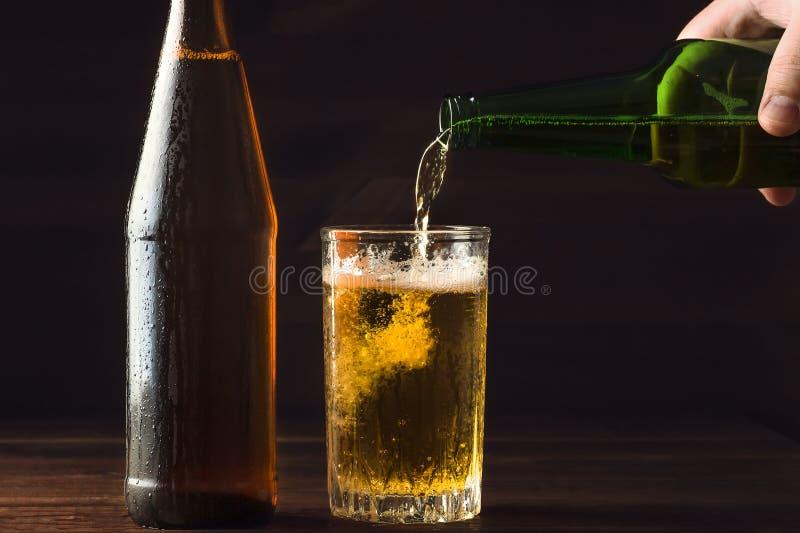 Att hälla skumma öl in i exponeringsglas rånar med droppar nära bootle för kallt öl på svart bakgrund arkivbild