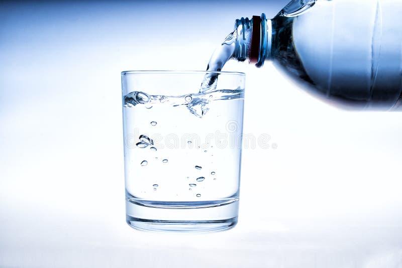Att h?lla bevattnar p? ett exponeringsglas p? vitbakgrund arkivbild