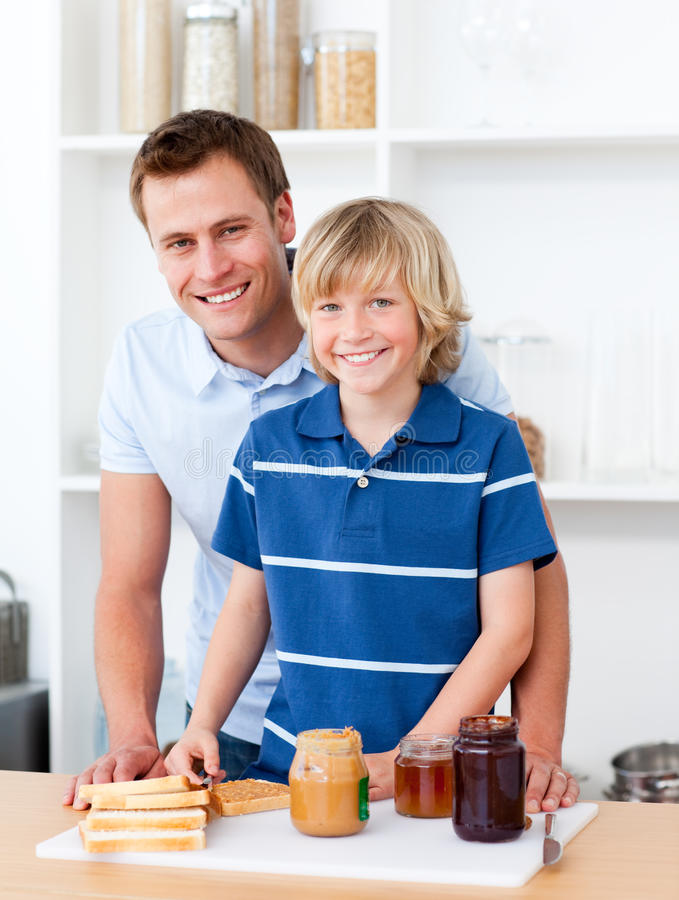 att hjälpa för frukostfader som är hans, förbereder sonen royaltyfri fotografi