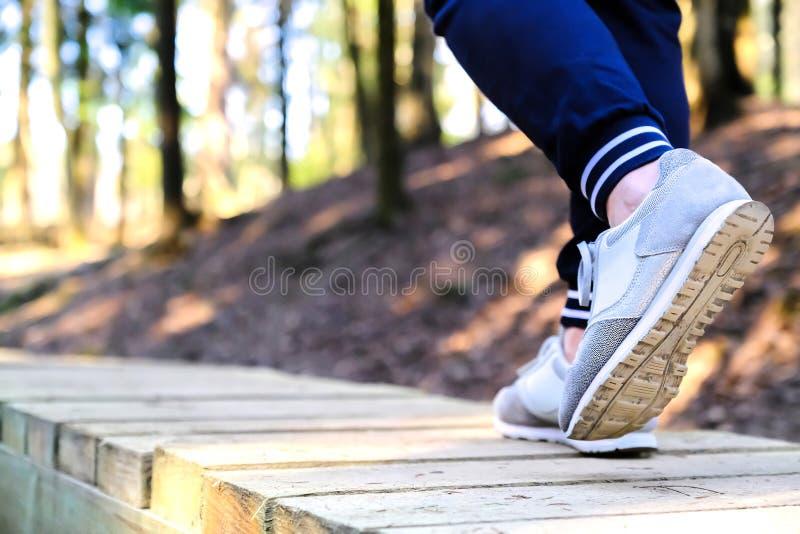 Att jogga i gymnastikskor på bron i parkerar Sport, hälsa och fysiskt kulturbegrepp royaltyfria bilder