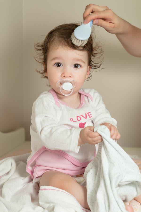 Att kamma för moder som är hennes, behandla som ett barn flickans hår med hårborsten efter dusch royaltyfri bild