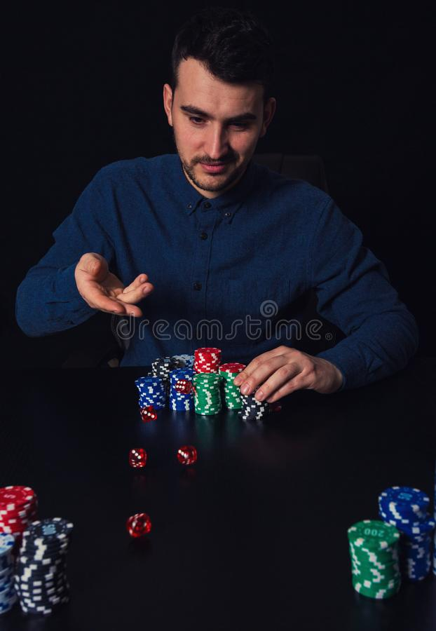 Att kasta för hasardspelare för ung man tärnar placerat på kasinotabellen Försökande lycka för hemfallen grabb och att slå vad ch arkivfoto