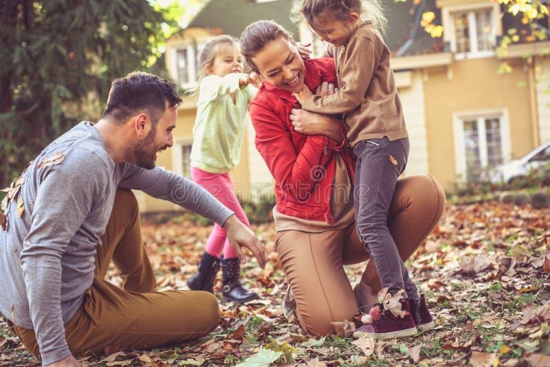 Att killa mamman är roligt Familj som spelar på framdelen av trädgården arkivfoto