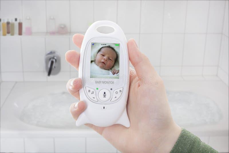 Att kontrollera för moder behandla som ett barn behandla som ett barn igenom bildskärmen, när det tar ett bad royaltyfri foto