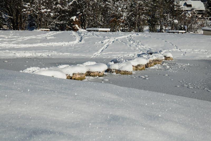 Att korsa den fryste sjön på snöig vaggar i scenisk idyll för vinter i Kranjska Gora i blå himmel, Slovenien royaltyfri foto