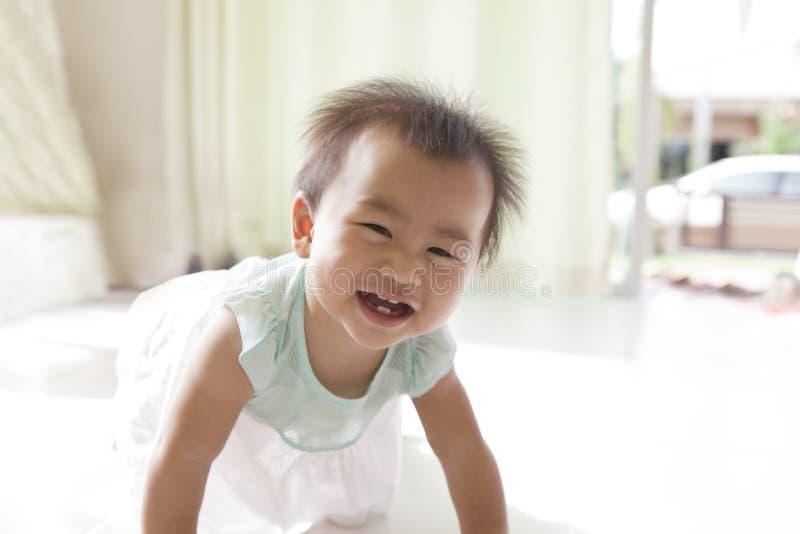 Att krypa av 10 månad behandla som ett barn med roligt vänder mot i hem- vardagsrum royaltyfria bilder