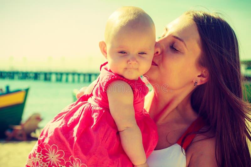 Att kyssa för kvinna behandla som ett barn på stranden nära vatten arkivfoto