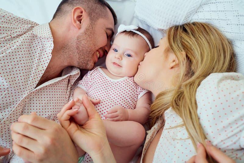 Att kyssa för mamma som och för farsa är deras, behandla som ett barn att ligga på sängen arkivfoton