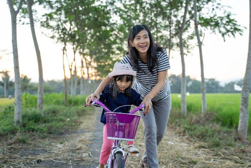 Att lära sig att cykla med mamma royaltyfria bilder