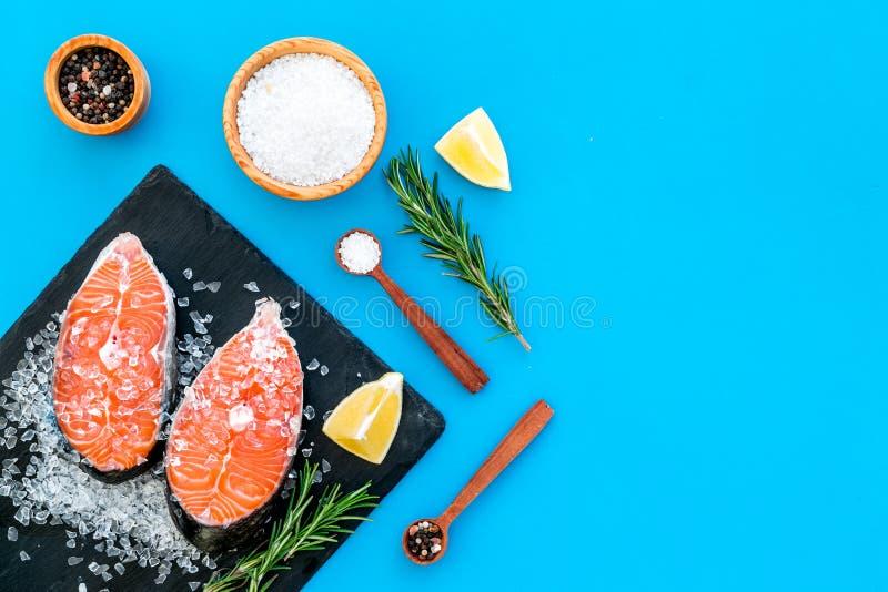 Att laga mat laxbiff från rå fisk på den svarta plattan med kryddor, rosmarin, citron och saltar på det blåa restaurangköksbordet royaltyfri bild