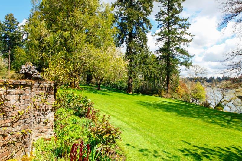 Att landskap nära sjön med stor grön gräsmatta och vaggar väggen fotografering för bildbyråer
