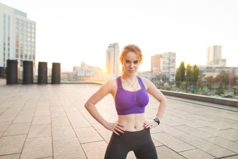 Att le överkanten och damasker för sportflicka den iklädda poserar på bakgrunden av soluppgången arkivfoto