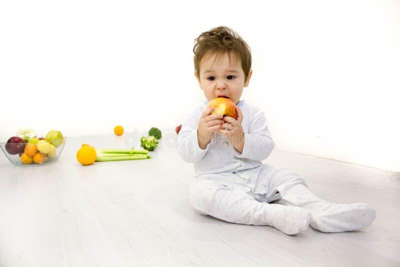 Att le behandla som ett barn äta bananen och många sorter av frukt och bunken med yoghurt royaltyfria foton